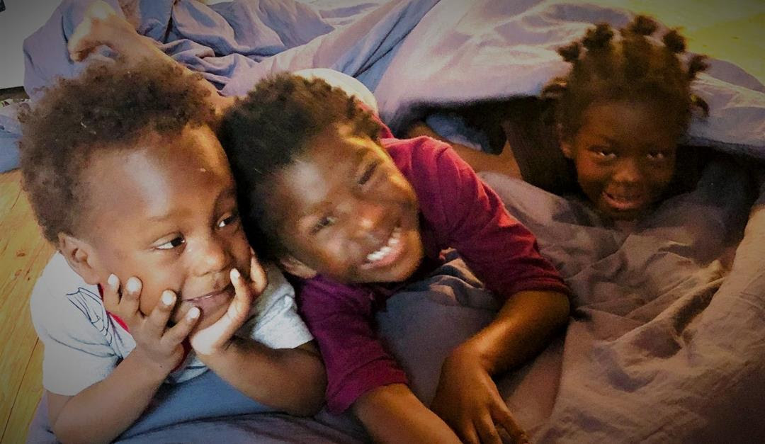 Three children smile as they lay under blankets