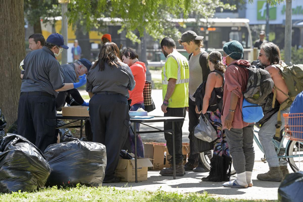 City officials ask people questions after they were moved from a homeless encampment
